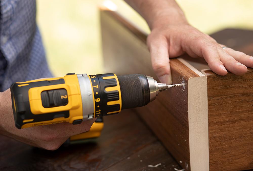man using drill on wood