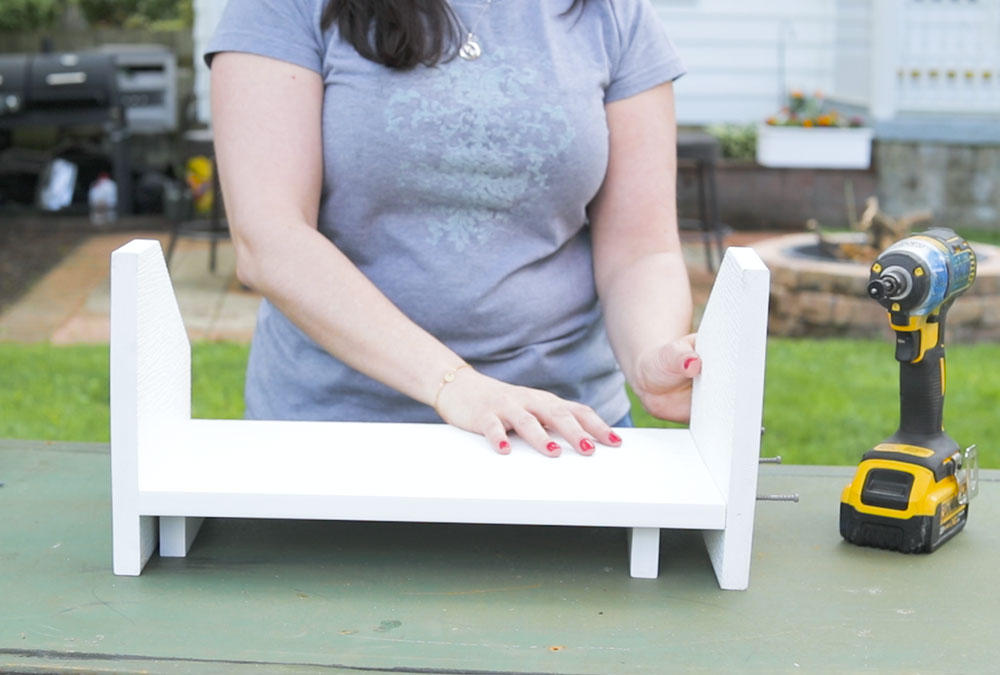 woman put together wood stand with drill