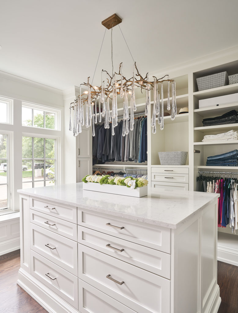 Closet with chandelier and island
